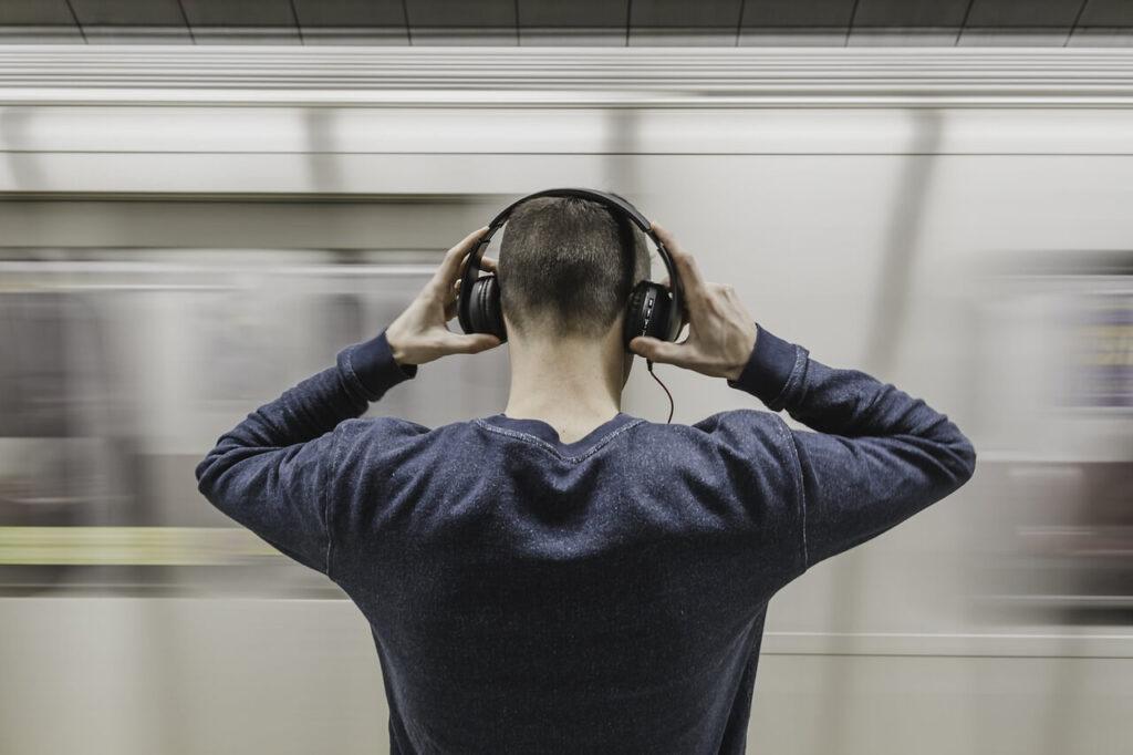 Mann mit Kopfhörern- Bahnfahrten bieten die Möglichkeit für Hörbücher